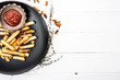 French potatoes on black plate with bowl of ketchup and sea salt. White wooden background.