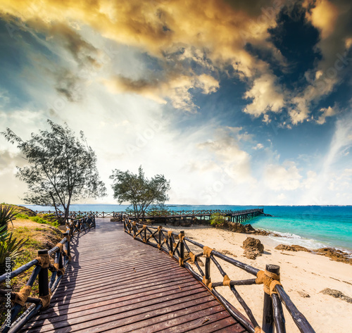 Deurstickers Zanzibar beautiful exotic landscape with wooden pier leading to the blue ocean in Africa at sunset
