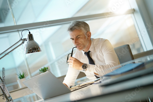 Fridge magnet Businessman working on laptop in office, being concerned