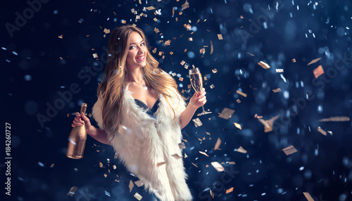 Well-dressed pretty woman in fur coat drinking champagne and standing in falling confetti with snow. - 184260727