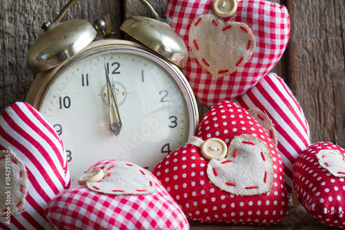 Time for love concept with alarm clock and handmade hearts