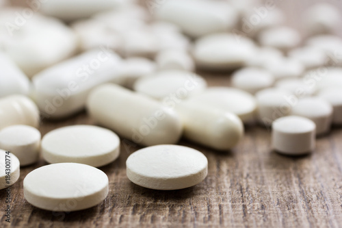 Heap of white capsules on wooden table.