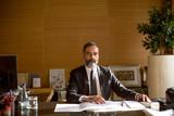 Senior businessman working on laptop in modern office - 184303152