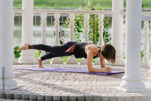 Fototapeta young woman doing yoga in summerhouse in summer