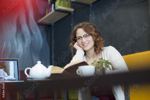 Giovane studentessa con gli occhiali sorride seduta davanti al suo libro in locale con i divani colorati
