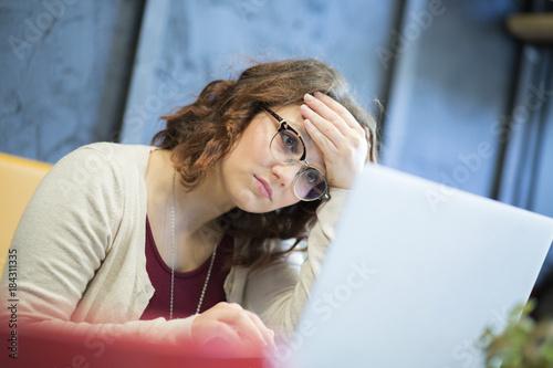 Giovane studentessa con gli occhiali guarda disperata mentre sta davanti al suo portatile