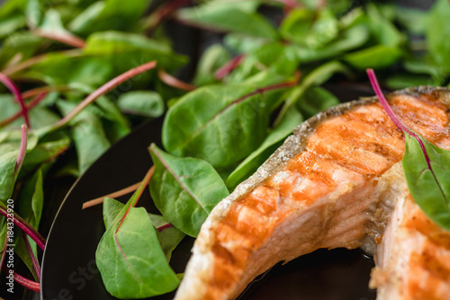 Plexiglas Steakhouse Top view on the grilled steak of salmon fish with lemon on a black plate and green leaves of chard salad.