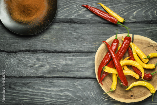 Tuinposter Hot chili peppers Red and yellow chili peppers on black wooden table. Black plate with powdered pepper. Overhead view at chili pepper on a wooden table. Place for text