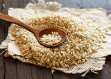 Pile of Brown rice with a wooden spoon - 184324341