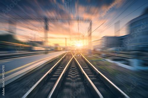 Stacja kolejowa z efekt rozmycia ruchu. Niewyraźne kolejowe. Przemysłowy konceptualny krajobraz z zamazaną stacją kolejową, budynkami, niebieskim niebem z kolorowymi chmurami i słońcem. Tor kolejowy. tło