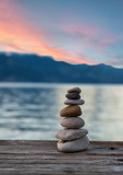 Stones pyramid on wooden pier, relaxation harmony background
