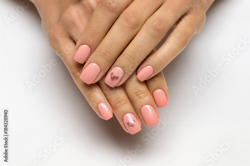 Poster Manicure pink manicure with golden hearts on nameless fingers on short nails