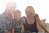 Parents and their son sit huddled in the living room and smiling - 184337704