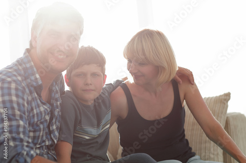 Parents and their son sit huddled in the living room and smiling