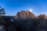 The supermoon peaks behind the rocky features of Smith Rock State Park during twilight hour in Central Oregon.