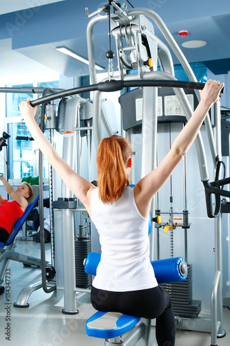 Póster Beautiful girl at the gym exercising on trainers. Beautiful girl