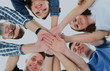 friendship, youth and people concept - group of smiling teenagers with hands on top of each other