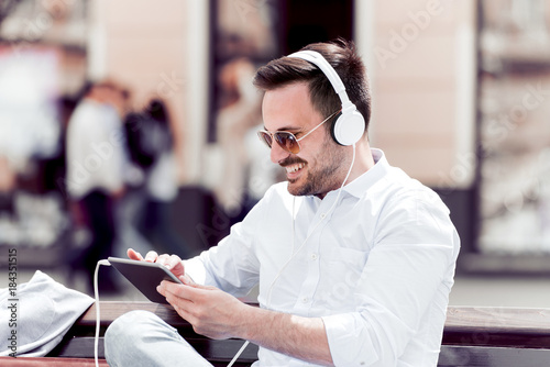 Man with headphones smiling and listening to music. Poster