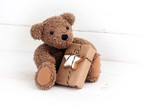Teddy bear with a Christmas present sitting on a white painted wooden background, copy space - 184354960