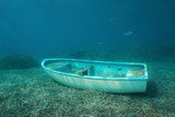 Underwater a small boat sunken on the seabed with leaves of Neptune grass and some fish, Mediterranean sea, Catalonia, Costa Brava, Spain - 184354962