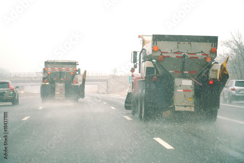 Snowplow spreading salt on the highway