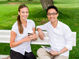 Portrait of smiling couple sitting in park and talking - 184378117