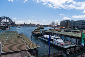 Hafenbecken von Sydney mit der Oper im Hintergrund aus Blickrichtung der Bahnstation