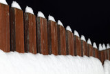 Part of the wooden fence of the backyard is covered with snow at night. - 184379728