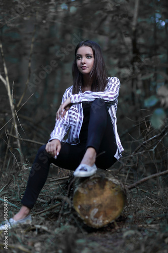 beautiful young woman sitting on a log Poster