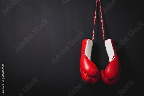 Professional red boxing gloves hanging on black background with copy space.