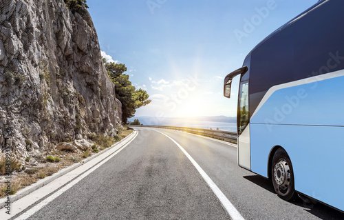 Fototapeta Tourist bus rushes along the country high-speed highway against the background of a mountain landscape.