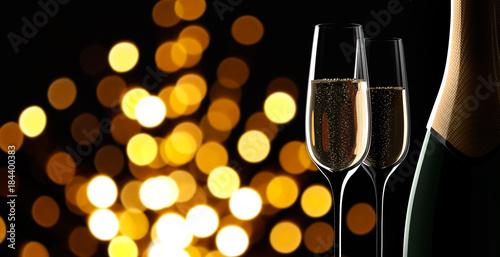 Gläser mit Champagnerflasche vor Lichtspiel