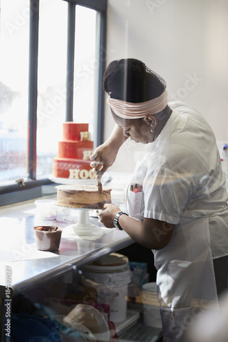 Young black woman frosting a cake at a bakery