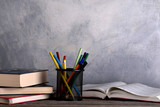 Group of school supplies and books on wooden table over a grey background - 184410391