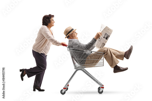Poster Elderly woman pushing a shopping cart with a mature man riding inside and readin