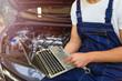 Mechanic Using Laptop While Examining Car Engine