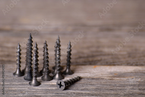 screws on a wooden background