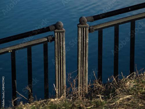 Plagát 川辺の柵の切れ目と、川面のさざ波。