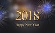 2018 card, New Year's eve illustration with fireworks and golden, glowing, sparkle 2018 Happy New Year text on grey background with blurry, colorful lights.