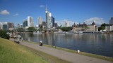 Skyline of the downtown in the city of Frankfurt Main. People jogging and riding bicycles at the riverwalk.   - 184433540