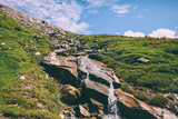 beautiful small waterfall on rocks and green grass in Indian Himalayas, Rohtang Pass