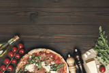 flat lay with italian pizza and various ingredients on wooden tabletop - 184445330