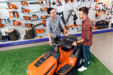 A consultant in a garden tools store shows a customer a lawn mower. - 184452132