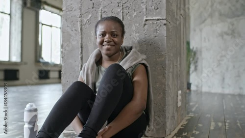 PAN of smiling African girl sitting on floor of fitness studio and smiling into camera