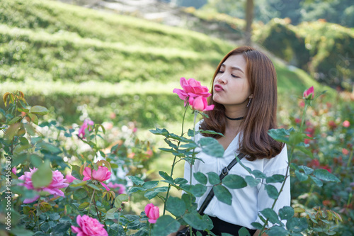 Wall mural Beautiful asia woman smelling a rose in garden