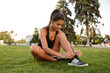 Portrait of young fitness girl tying her shoelaces
