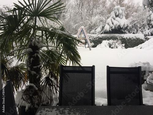 Plexiglas Zwart Plötzlicher Wintereinbruch im Garten mit Palme und Gartenmöbeln