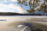 Winter landscape in Finland. Snowy ground and lake ice with sunlight. Beautiful moment on a cold morning. - 184477985