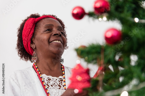 Old black woman decorating the christmas tree Poster