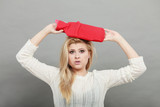 Woman holding red hot water bottle on head - 184502145